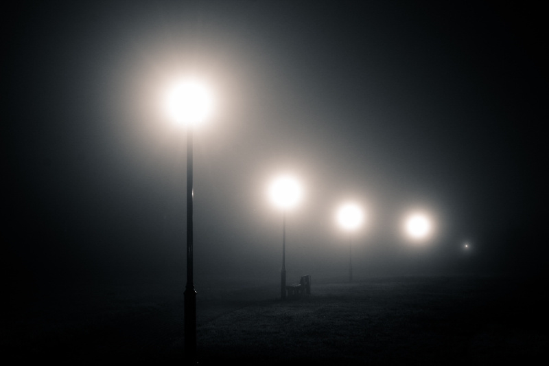 A foggy park scene, with streetlamps and a bench in the fog